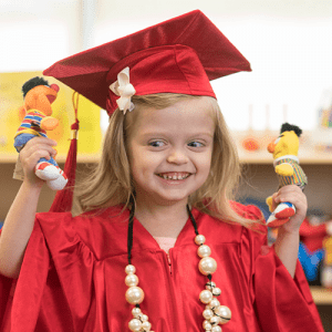 A Pre-K aged little girl in a red cap and gown smiles at two little Sesame Street finger puppets.